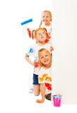 Three funny kids in painted shirts. Hold pose near wall stock photos