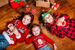 Three funny little sisters lie on the floor at home. Near Christmas tree stock photography