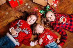Three funny little sisters lie on the floor at home. Near Christmas tree stock images