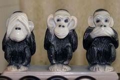 Three funny monkey statues in various poses Royalty Free Stock Images