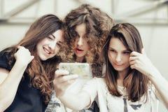 Three funny pretty girls make self photo Royalty Free Stock Photo