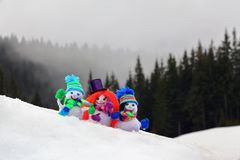 Three funny, small, knitted with a crochet hook snowmen. Royalty Free Stock Image
