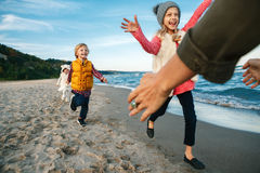 Three funny smiling laughing white Caucasian children kids friends playing running to mother parent adult on ocean sea beach. Group portrait of three funny Stock Images