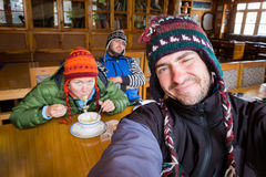 Three funny tourists nepali guesthouse dining room eating noodle. Selfie of three funny comic tourists wearing warm clothes sitting nepali guesthouse dining room Royalty Free Stock Photo