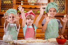 Three funny young child  play with a dough in the kitchen Royalty Free Stock Photo