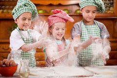 Three funny young child shaking hands with flour in the kitchen Stock Photography