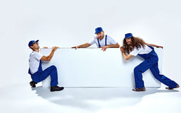 Three funny craftsmen holding an empty board. Three funny young craftsmen holding an empty board Stock Image