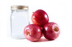 Three gala apples beside a mason canning jar Royalty Free Stock Image