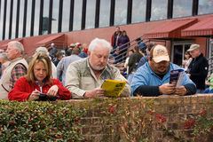 Three Gamblers at the Horse Race Track. Three gamblers planning their next wager at the Oaklawn Horse Race track in Hot Springs, Arkansas Stock Photo