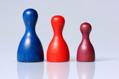 Three game figurines. Three wooden playing figurines next to each other by size Royalty Free Stock Photography