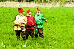 Three garden gnomes enjoy children Royalty Free Stock Image