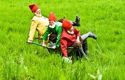 Three garden gnomes enjoy children Royalty Free Stock Images