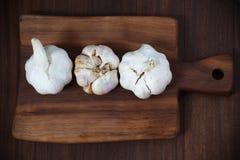 Three garlic bulbs on cutting board Stock Photography