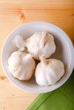 Three garlic bulbs in white ceramic bowl Royalty Free Stock Image