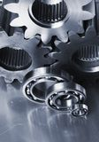Three gear-wheels and ball-bearings. Cogs, ball-bearings against brushed aluminum royalty free stock images