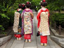 Three geisha. Wearing kimonos in a traditional street of Kyoto,Japan Royalty Free Stock Images