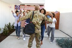 Three generation African American  family welcoming back millennial soldier returning home,back view. Three generation black family welcoming back millennial royalty free stock images