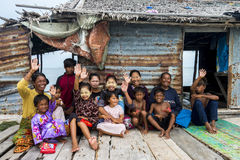 Three generation of Bajau tribe sit outside waving hands outside their wooden hut. Royalty Free Stock Photography
