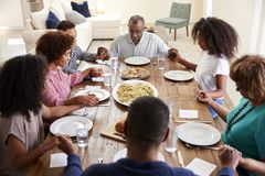 Three generation African American  family holding hands and saying grace at table before dinner,elevated view. Three generation black family holding hands and stock photos