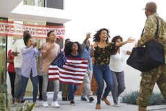 Three generation African American  family running out of house to welcome soldier returning home, low angle view. Three generation black family running out of royalty free stock image