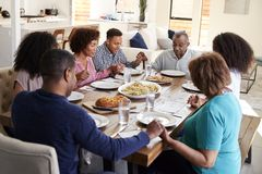 Three generation African American  family sitting at dinner table holding hands and saying grace before meal. Three generation black family sitting at dinner royalty free stock photography