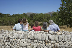 Three Generation Family Against Stone Wall Stock Images