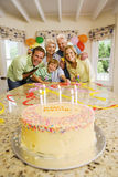 Three generation family celebrating birthday at home, smiling, portrait, birthday cake on table in foreground Stock Photo