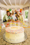 Three generation family celebrating birthday at home, smiling, portrait, birthday cake on table in foreground royalty free stock photos