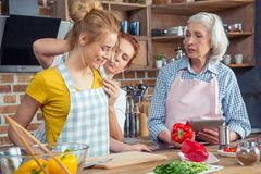 Three-generation family cooking together. In kitchen stock photos