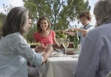 Three Generation Family Dining In Garden Stock Photos