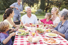 Three Generation Family Enjoying Barbeque In Garden Together Stock Images