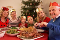 Three Generation Family Enjoying Christmas Meal. At Home Smiling royalty free stock photo