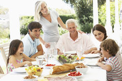 Three Generation Family Enjoying Meal Outdoors Stock Photos