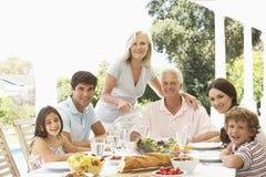 Three Generation Family Enjoying Meal Outdoors Stock Photo