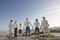 Three Generation Family Holding Hands On Seashore. Rear view of three generation family holding hands on seashore Stock Photography