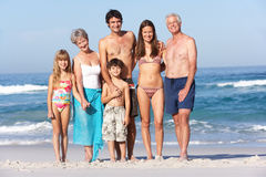 Three Generation Family On Holiday At The Beach. Three Generation Family On Holiday Walking Along Beach Smiling At Camera Stock Photo