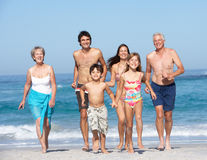 Three Generation Family On Holiday On Beach. Three Generation Family On Holiday Walking Along Beach Having Fun Stock Photography