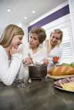 Three generation family in kitchen cooking lunch. Three generation family in kitchen serving lunch Royalty Free Stock Photo