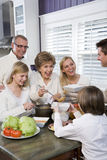 Three generation family in kitchen eating lunch. Talking and laughing royalty free stock photos
