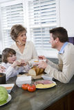 Three generation family in kitchen eating lunch Royalty Free Stock Photos