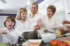 Three generation family in kitchen eating lunch Stock Photos