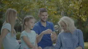 Three generation family playing with soap bubbles stock video footage