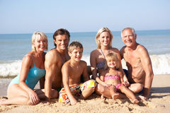 Three generation family pose on beach. In the sun royalty free stock image