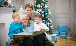 Three generation family reading a book Royalty Free Stock Photo
