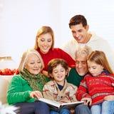 Three generation family reading stock images