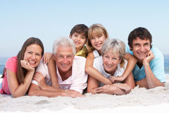 Three Generation Family Relaxing On Beach Stock Photos