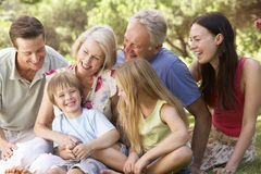 Three Generation Family Sitting In Park Together Stock Photos