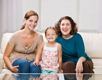 Three generation family sitting on sofa Stock Photo