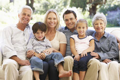 Three Generation Family Sitting On Sofa At Home stock images