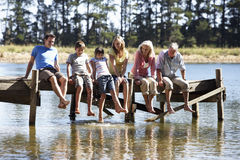 Three Generation Family Sitting On Wooden Jetty Looking Out Over Lake Royalty Free Stock Photos